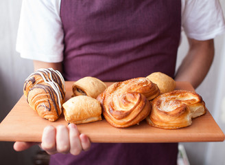 Baker showing tray of fresh croissant and buns in the kitchen