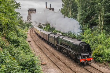 A Steam Train In Britain Passing A Power Station