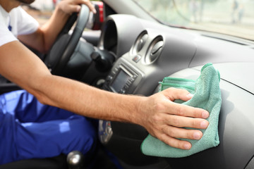 Man cleaning automobile dashboard with duster in vehicle. Car wash service