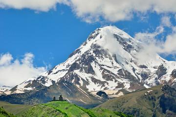 Mount Kazbek (5047m), the third-highest peak in Georgia, bordering Russia, with the Gergeti Trinity Church on its slopes. Khevi-Kazbegi region. Georgia, Caucasus