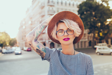 Portrait of pretty blonde girl with short hair posing to the camera on the steet in city. She wears gray checkered  dress, glasses,  tattoo.  She holds hat on head and looks to the camera.