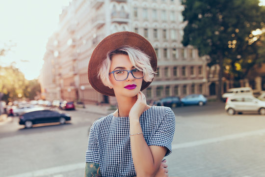 Portrait of pretty blonde girl with short hair posing to the camera on the steet in city. She wears gray checkered  dress, glasses, hat and has purple lips.