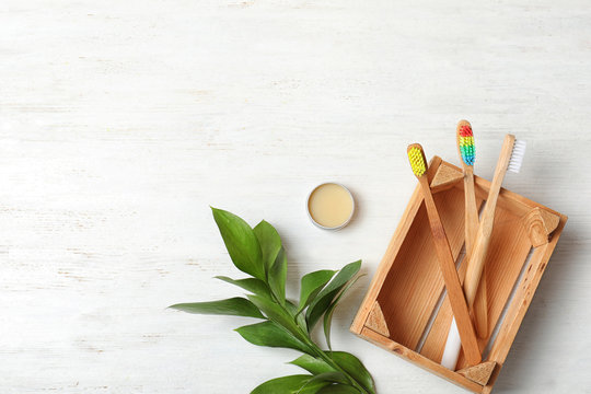 Flat lay composition with bamboo toothbrushes and space for text on white wooden background