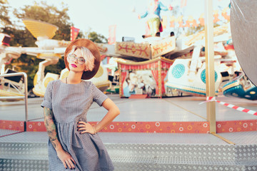 Pretty blonde girl with short haircut is posing in amusement park on carousel background. She wears checkered dress,  glasses, hat and has purple lips.