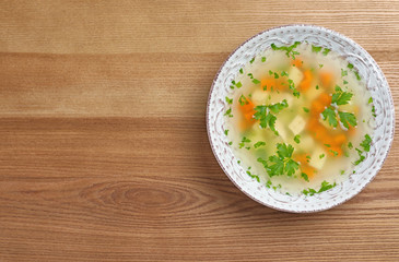 Bowl of fresh homemade soup to cure flu on wooden background, top view with space for text