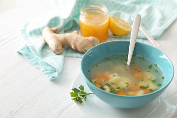 Bowl of fresh homemade soup to cure flu on wooden table
