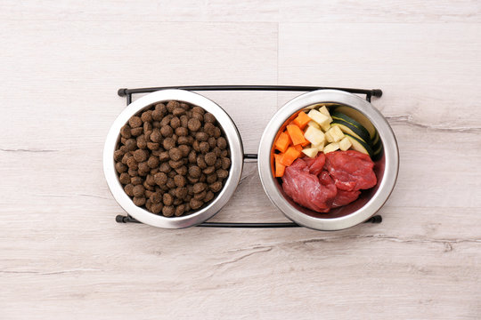 Bowls with dry and natural dog food on light background, top view
