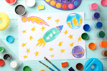 Flat lay composition with child's painting of spaceship on table