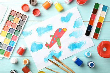 Flat lay composition with child's painting of airplane on table