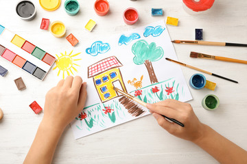 Girl painting picture of house on table, top view