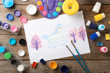 Flat lay composition with child's painting of unicorn on table