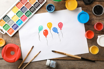 Flat lay composition with child's painting of balloons on table