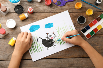 Girl painting picture of cat on table, top view