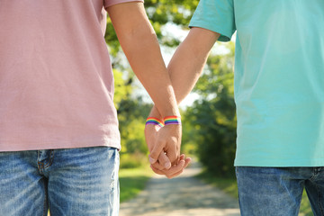 Gay couple with wristbands holding hands outdoors, closeup