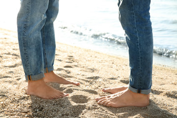 Gay couple standing barefoot on beach, closeup