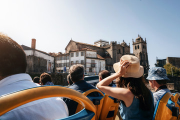 Porto, Portugal. Tourists on open top sightseeing bus Hop on hop off in explore city. Cathedral Seu on the background Fototapete