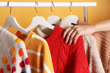 Fototapete - Woman choosing sweater on rack against color background, closeup
