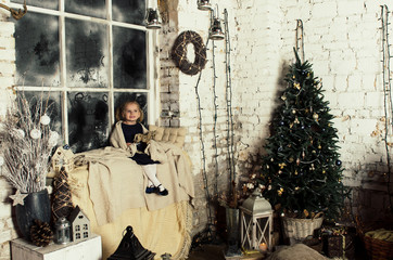 little girl sitting near Christmas decorated window