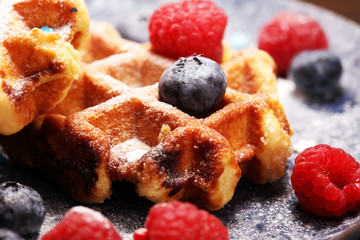 waffles with fresh blueberries, sugar and raspberries.