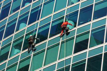 Scrubber washing skyscraper windows, rear view