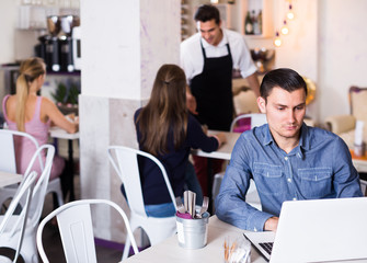 concentrated young man using laptop in modern cafe