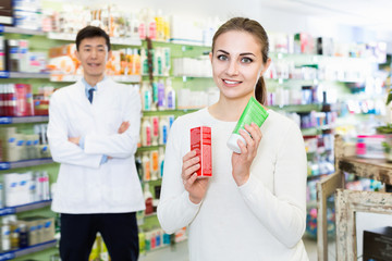 Portrait of woman client who is satisfied of recommended medicines in pharmacy.