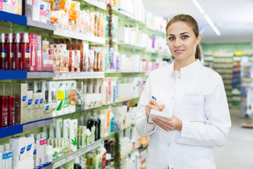 Female is looking medicine with notebook near shelves in apothecary
