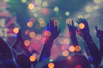 Audience with hands raised at a music festival and lights