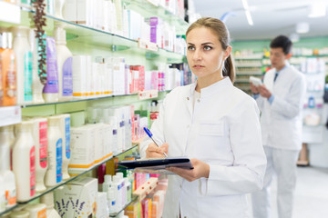 Female pharmacist checking medicine with notebook in  drugstore