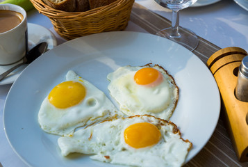 Plate with fried eggs at plate and cup of coffee,  breakfast in cafe