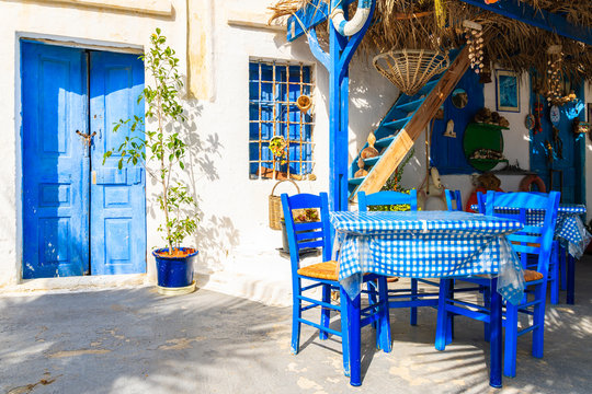 Table in front of typical Greek house on street of Finiki village, Karpathos island, Greece