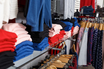 Stand with various clothes in clothing shop