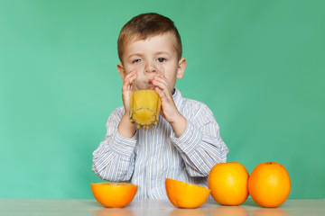 Portrait of happy little boy drinking orange juice.