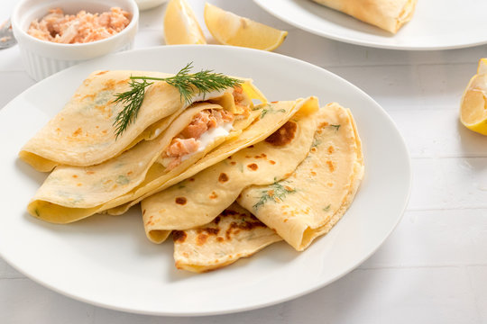 Crepes filled with dill, cream cheese and smoked salmon on white plate.