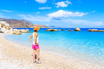 Young woman standing on Apella beach and looking at sea, Karpathos island, Greece