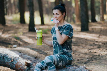 Sporty attractive slender young woman sitting and eating a piece of a protein bar as she takes a break from her daily jog in the forest