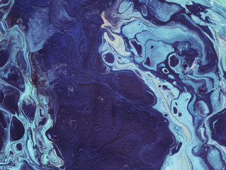 Very beautiful textural background. Light turquoise paint flows in dark blue with the addition of beige and gold paint. The style includes curls of marble or pulsations of agate with bubbles and cells