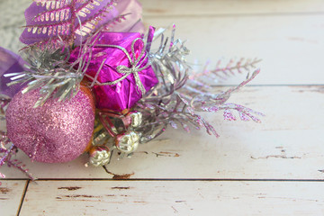 Background new year, Christmas. Christmas decoration, purple branch with balls and gift isolated on gray textured knitted background. Copy space. The festive side.
