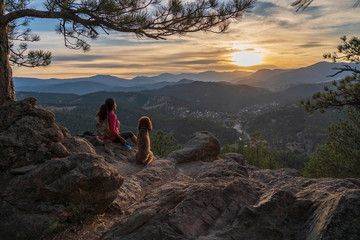 A hispanic woman is hiking with a dog, at sunset, in the Rocky Mountains near Denver, Colorado, USA Wall mural