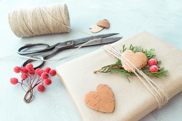 Christmas wrapping. Gift box, present with craft wrapping paper, twine, coniferous branches, red berries and scissors on grey concrete background. Wrapping christmas gift pack, decorations