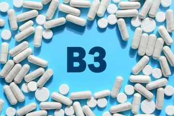 Vitamin B3 text in white capsules frame on blue background. Pill with Niacin. Dietary supplements and medication