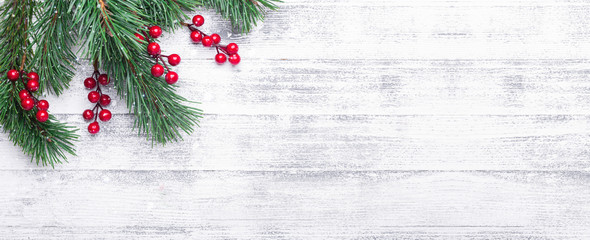 Christmas background with tree branches and holly berries. White wooden table. Snowfall drawing...