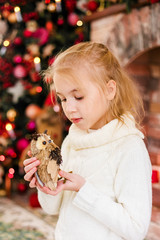 Christmas portrait of happy blonde child girl in white sweater holding toy owl near the Christmas tree and wooden toy horse. New Year Holidays