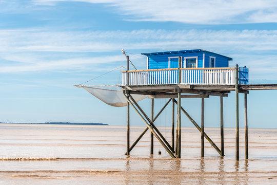 une cabane de pêcheur bleue sur pilotis au dessus d'une mer  marron