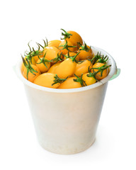 plastic bucket full of fresh yellow tomatoes isolated on the white