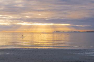 Landscape Scenery of Takapuna Beach Auckland, New Zealand; Sunrise time some people are enjoying paddle-boarding