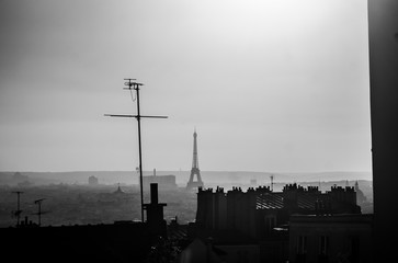 Eiffel Tower in black and white seen from the Montmartre neighborhood with simple houses and rooftops on the amazing landscape of Paris, France. A scene showing the Parisian life in Europe.