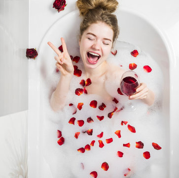 Relaxing woman smiling in hot bath with bubbles. Beautiful woman in bath with rose petals drinking wine. Woman in bath with foam and petals. Attractive girl enjoy Spa treatments for skin. Happy smile.