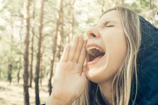 Attractive girl screaming in the forest. Close-up of open mouth. Scream concept as an illustration of helping children with problematic pronunciation or learning difficulties with skills