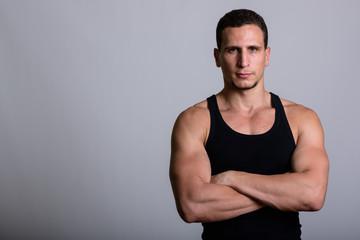 Studio shot of young muscular Persian man looking at camera with